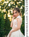 Young girl in wedding dress in park posing for 37628109