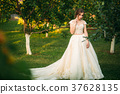 Young girl in wedding dress in park posing for 37628135