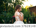 Young girl in wedding dress in park posing for 37628148