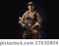 special forces soldier poses with a rifle on a black background 37630804