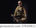 special forces soldier poses with a rifle on a black background 37630811