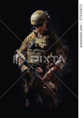 special forces soldier poses with a rifle on a black background 37630815