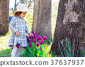 Toddler girl playing with tulips outside 37637937