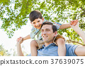Mixed Race Father and Son Playing Piggyback Together in the Park 37639075