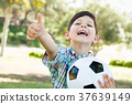 Cute Young Boy Playing with Soccer Ball and Thumbs Up Outdoors i 37639149