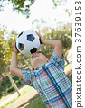 Cute Young Boy Playing with Soccer Ball Outdoors in the Park. 37639153