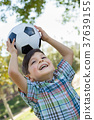Cute Young Boy Playing with Soccer Ball Outdoors in the Park. 37639155