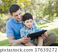 Happy Father and Son Playing on a Computer Tablet Outside. 37639272