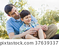 Loving Father Puts a Bandage on the Elbow of His Young Son in th 37639337