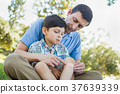 Loving Father Puts a Bandage on the Elbow of His Young Son in th 37639339