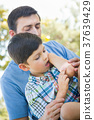 Loving Father Puts a Bandage on the Elbow of His Young Son in th 37639429