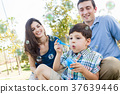 Young Boy Blowing Bubbles with His Parents in the Park. 37639446
