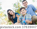 Young Boy Blowing Bubbles with His Parents in the Park. 37639447