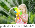 Adorable little girl playing with water gun on hot summer day 37666421