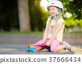 Pretty little girl learning to skateboard on beautiful summer day in a park 37666434