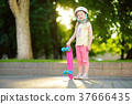 Pretty little girl learning to skateboard on beautiful summer day in a park 37666435