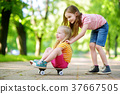 Two pretty little girls learning to skateboard on beautiful summer day in a park 37667505