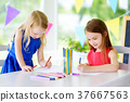 Two cute little sisters drawing with colorful pencils at a daycare. Creative kids painting together. 37667563