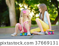 Two pretty little girls learning to skateboard on beautiful summer day in a park.  37669131