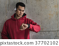 Sport man wearing earphone, looking at his watch 37702102