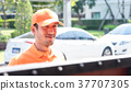Orange uniform Delivery man is waiting at the gate 37707305
