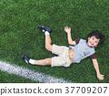 Little boy is lying down on soccer field top view 37709207