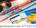 Toy train, tickets, passport and bank card on laptop or notebook 37710114