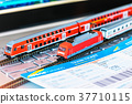 Toy train, tickets, passport and bank card on laptop or notebook 37710115