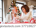Senior couple in sweaters wrapping Christmas gifts 37710627