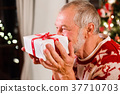 Senior man in front of Christmas tree holding a 37710703