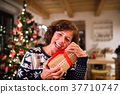 Senior woman in front of Christmas tree holding a 37710747