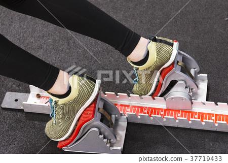Sprinter in spikes in the blocks indoor 37719433