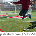 Front view of athlete jumping over yellow hurdles 37719550