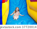 Child jumping on playground trampoline. Kids jump. 37720014