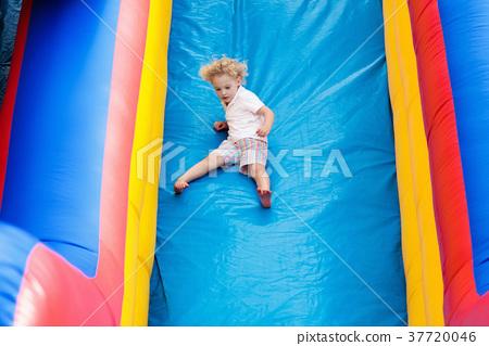Child jumping on playground trampoline. Kids jump. 37720046