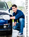 Proud car owner cleaning the headlamps 37746703