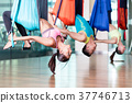 Fit young woman practicing aerial yoga during 37746713