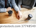Students couple having a romatic lunch indoors holding hands close-up 37748540