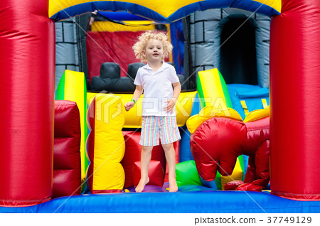 Child jumping on playground trampoline. Kids jump. 37749129