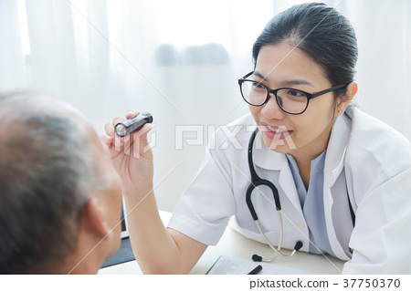 Female Doctor checking to senior man patient eyes. 37750370