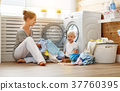 Happy family mother   housewife and   baby son in   laundry load 37760395