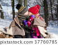 Little girl kissing boy with gift outdoors 37760785