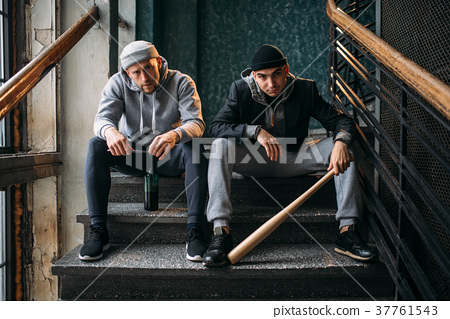 Two male robbers are sitting on the stairs 37761543