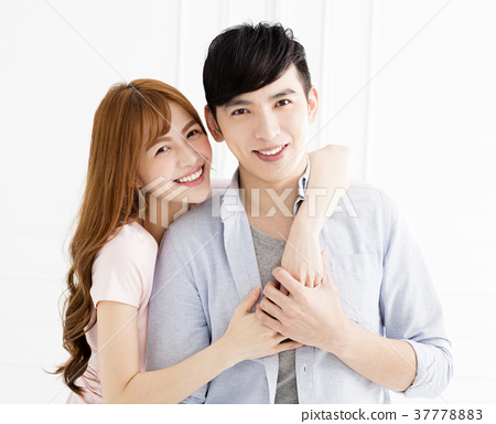 happy young asian couple hugging in living room 37778883