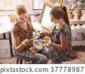 Artist painting on easel in studio. Authentic 37778987