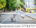 mom with a stroller crosses the road 37784757