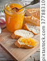 orange jam in a glass jar and bread 37788310