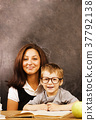 little cute boy with young teacher in classroom 37792138