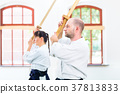 Man and woman having Aikido sword fight 37813833
