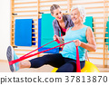 Senior woman with stretch band at fitness 37813870
